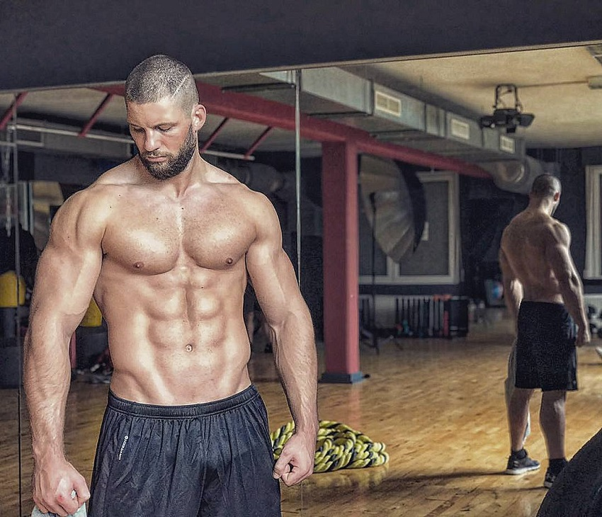Florian Munteanu standing shirtless in a training room looking muscular and fit