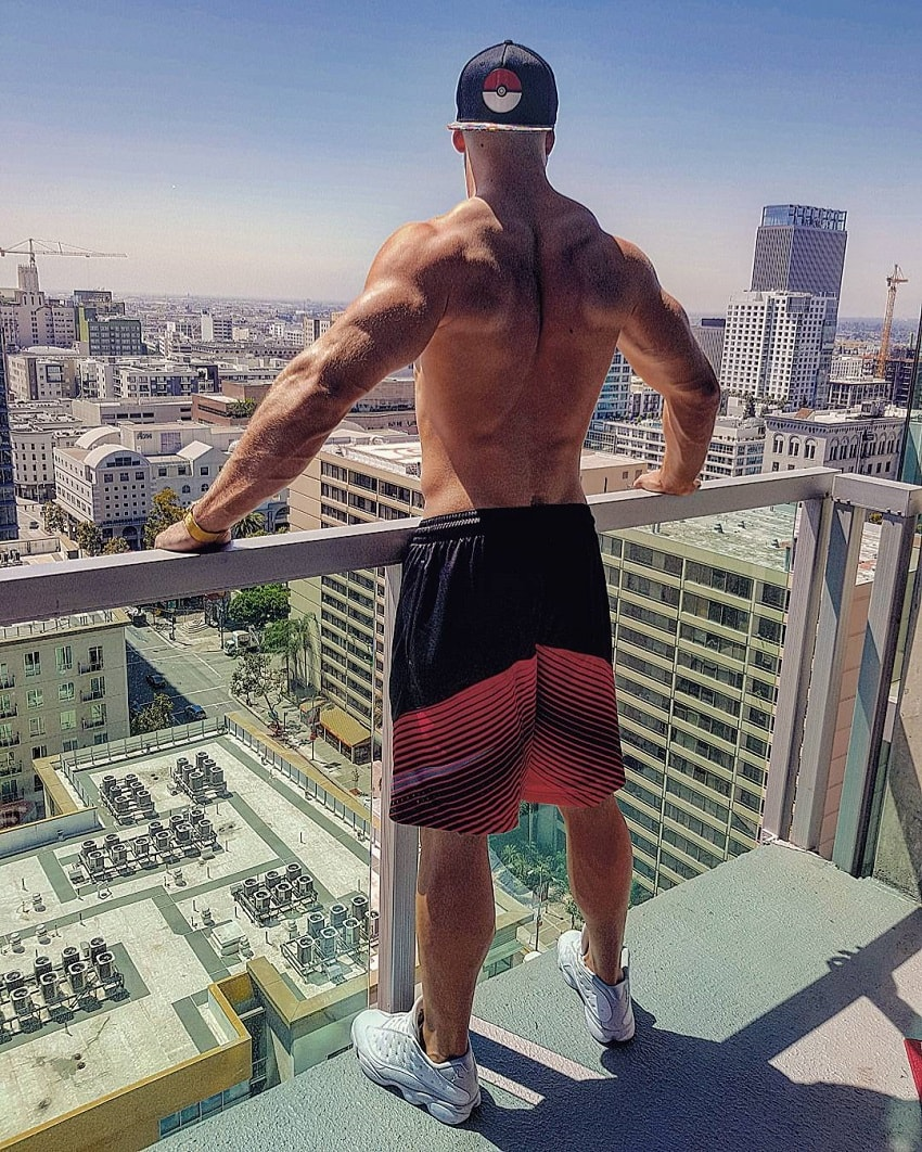 Florian Munteanu standing on a balcony overlooking a big city with skyscrapers during the sunny day