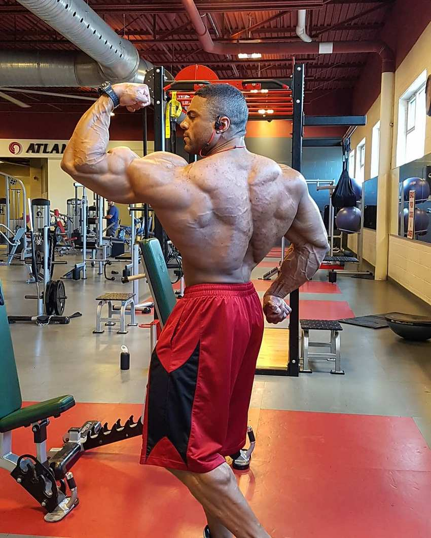 Henri-Pierre Ano flexing his back and biceps for the camera
