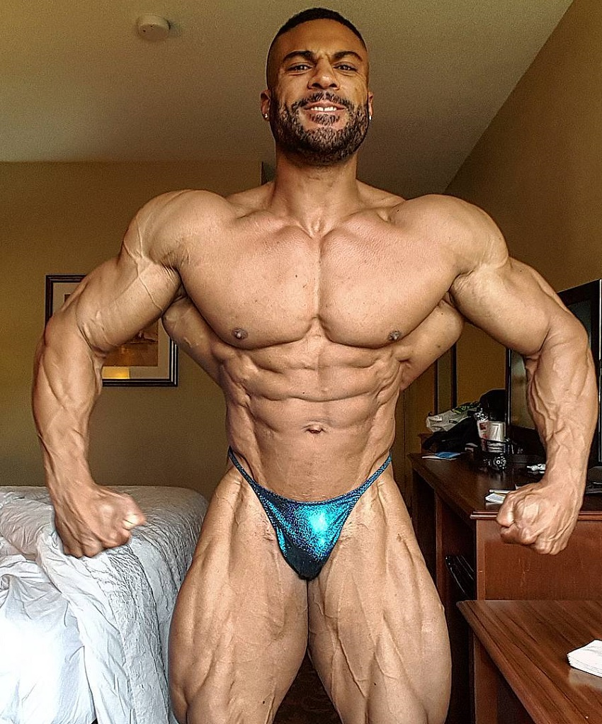Henri-Pierre Ano posing shirtless for a photo looking muscular and big