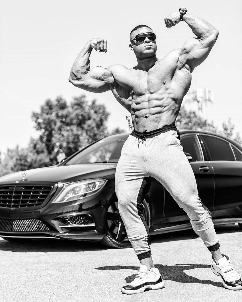 Henri-Pierre Ano flexing his biceps in front of his luxurious car