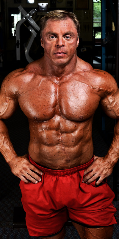 John Meadows posing shirtless for a photo looking big and ripped