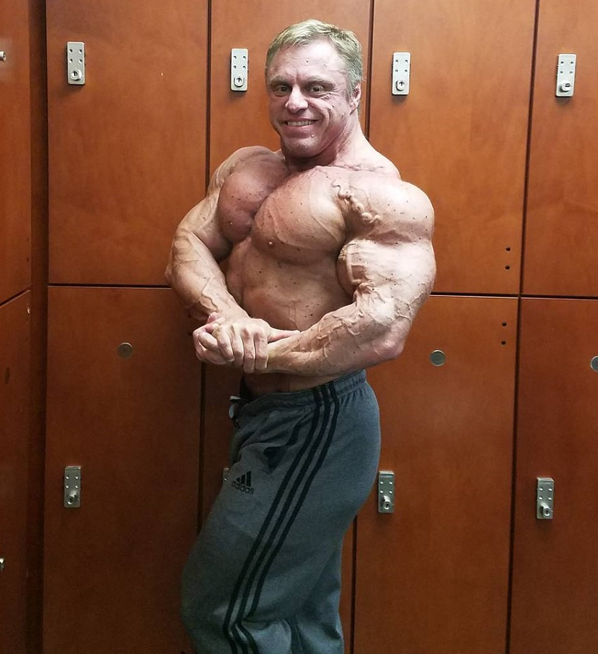 John Meadows doing a shirtless side chest pose in a gym locker room