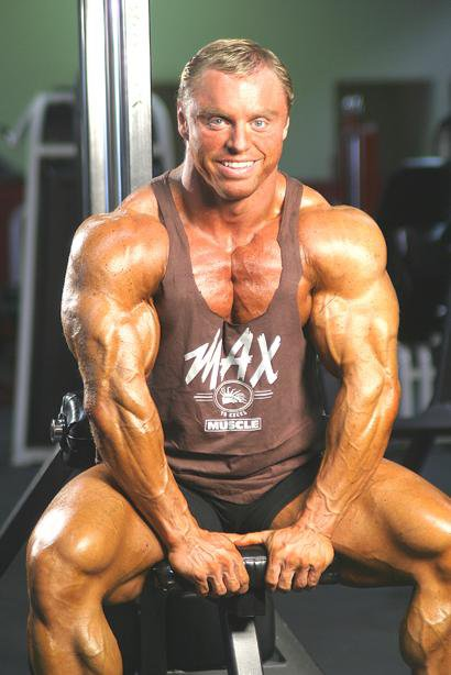 John Meadows sitting on a bench in tank top showing off his muscular upper body
