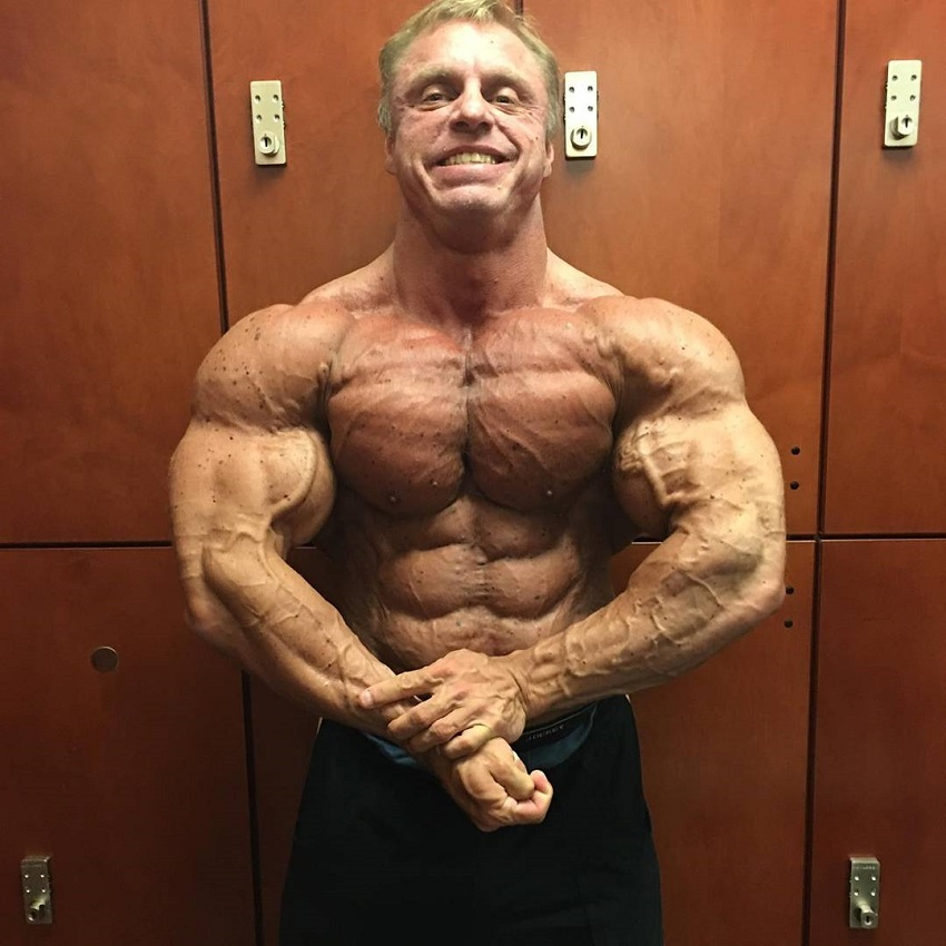 John Meadows doing a shirtless most muscular pose in a gym locker room