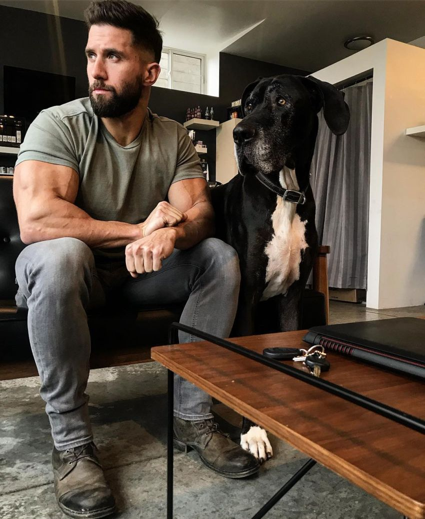 Julian Smith with his dog in his house, looking in the distance, looking healthy and fit