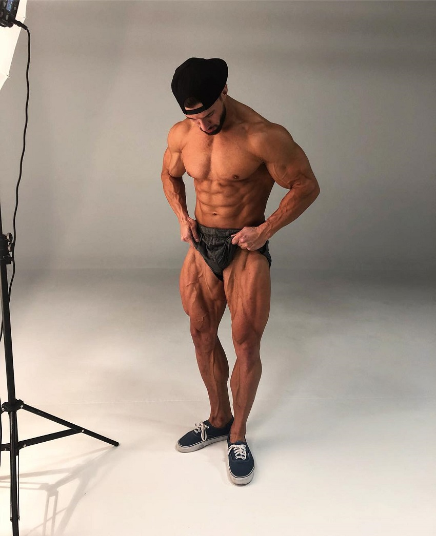 Julian Smith doing a photoshoot posing shirtless looking ripped