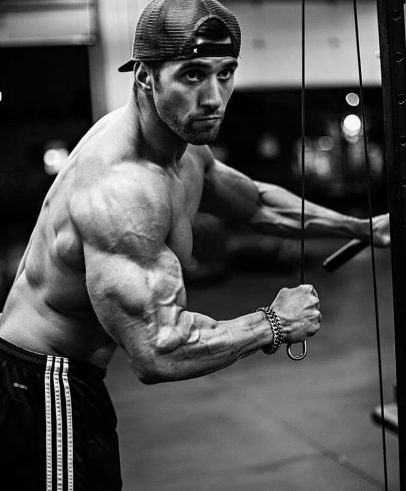 Julian Smith training shirtless with cables in a gym looking ripped