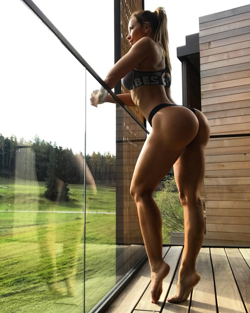 Kate Krasavina standing on a balcony in a bikini, showing off her curvy and lean physique