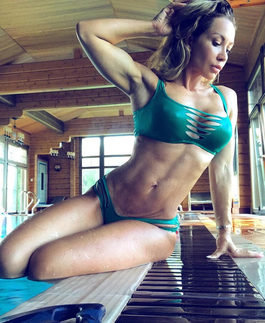 Kate Krasavina sitting by the pool in a green bikini, looking fit, lean, and aesthetic