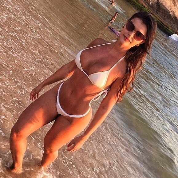 Liz Amorim Caria standing in shallow waters wearing a white bikini looking fit and lean