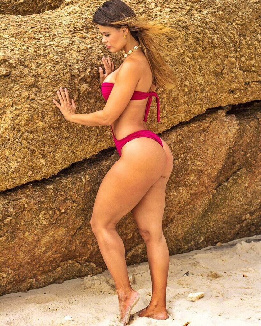 Liz Amorim Caria standing by the rock on the beach looking fit
