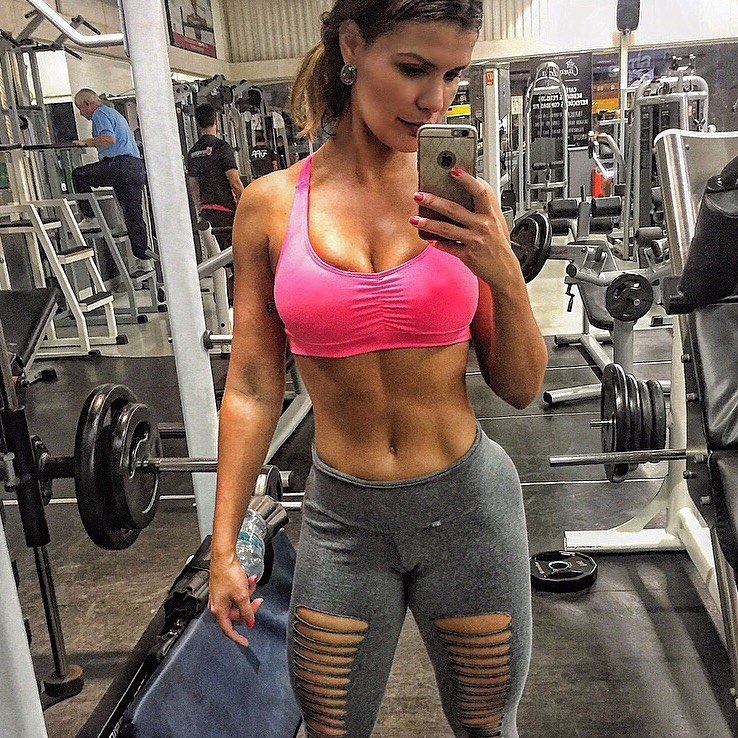 Liz Amorim Caria taking a selfie of her lean abs in a gym