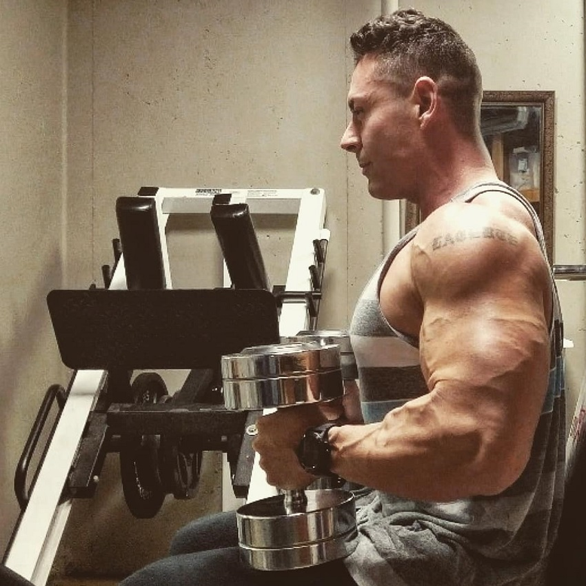 Micah Lacerte sitting on a bench with dumbbells in his hands looking ripped and muscular