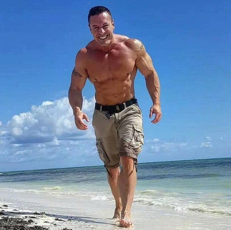 Micah Lacerte enjoying the sun on the beach and smiling for a photo