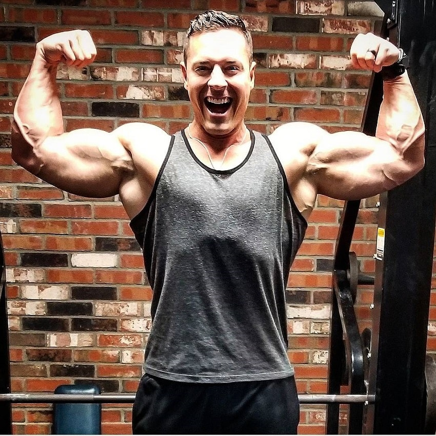 Micah Lacerte flexing his biceps and smiling for a photo