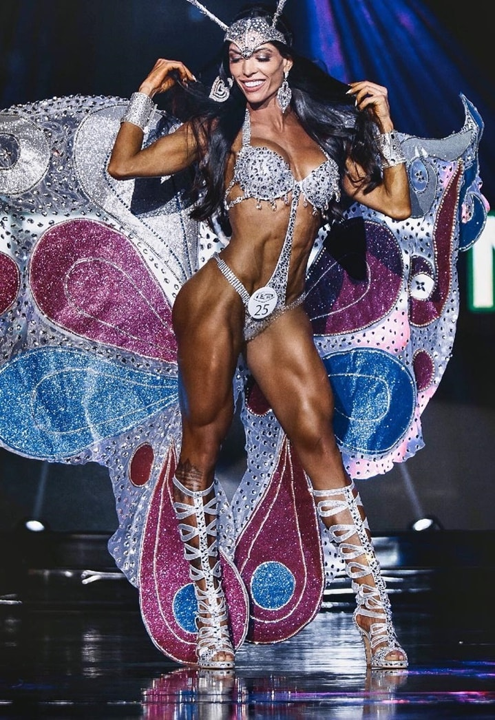 Muri Rodrigues posing on the stage in a WBFF competition, looking conditioned and fit