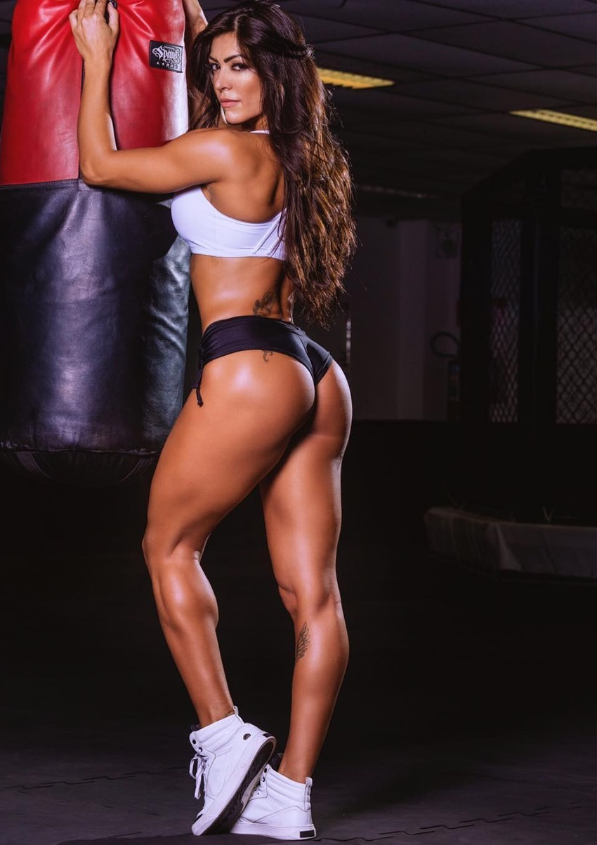 Muri Rodrigues posing by the boxing bag, showing off her curvy legs and glutes