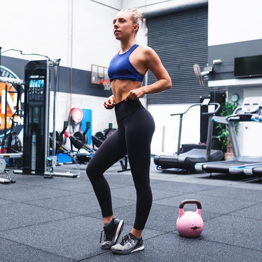 Sarah Day flexing in a gym looking fit and healthy