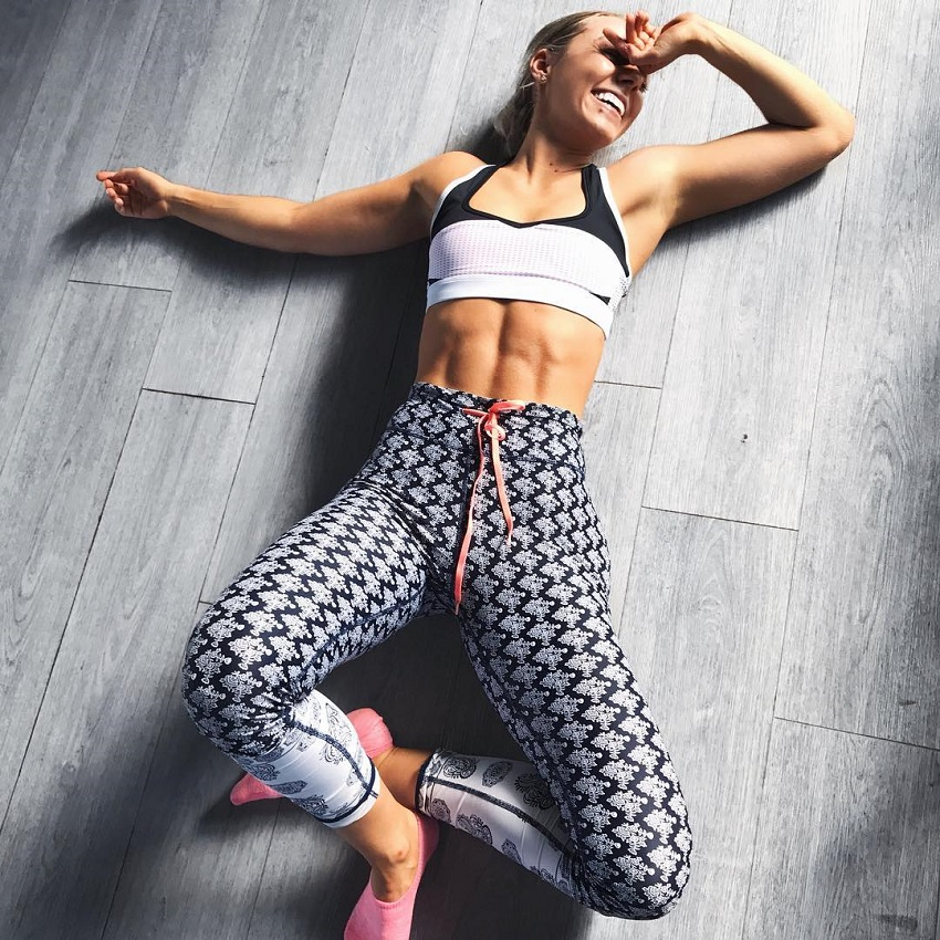Sarah Day lying on the floor and smiling while wearing her gym wear looking fit and lean