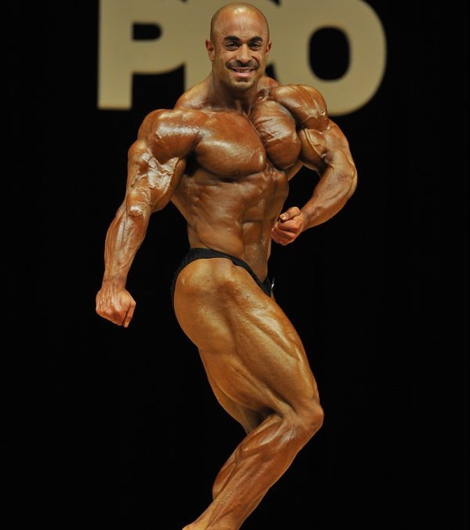 Sasan Heirati doing a 'Phil Heath' iconic side flex pose on a bodybuilding stage