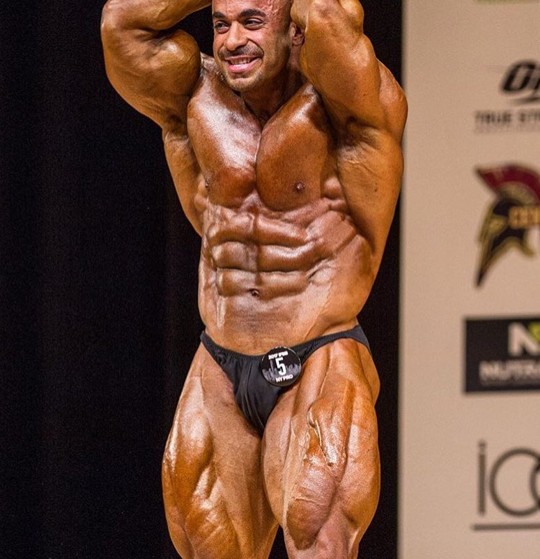 Sasan Heirati doing an ab and leg most muscular pose on a bodybuilding stage