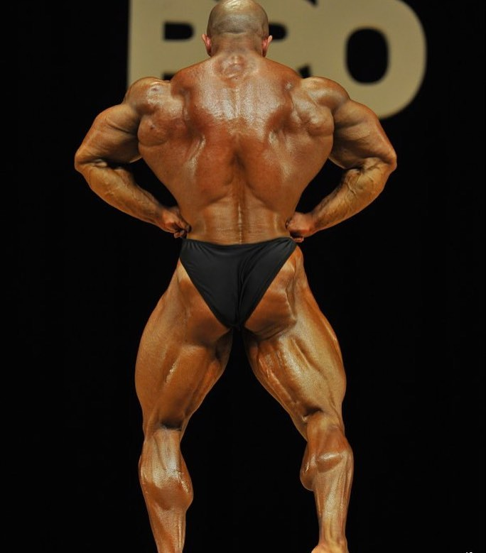 Sasan Heirati performing a rear lat spread pose on a bodybuilding stage