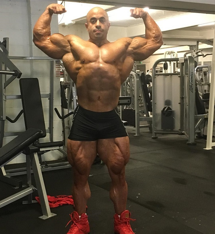 Sasan Heirati doing a shirtless front double biceps pose in a gym