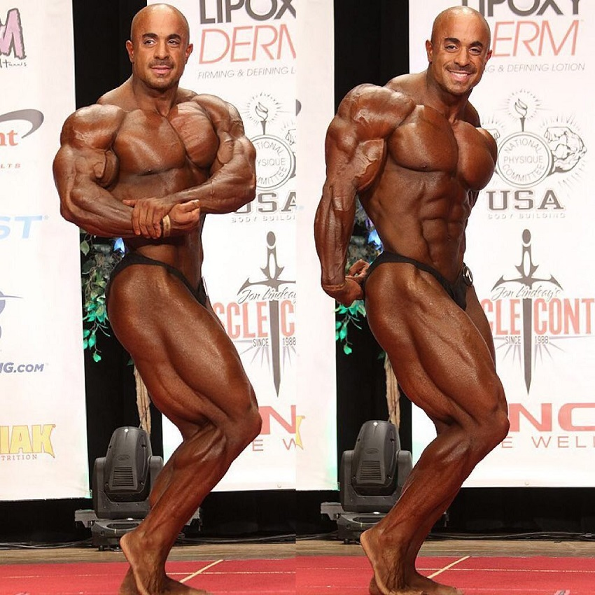 Sasan Heirati doing a side chest and side triceps pose on a bodybuilding stage