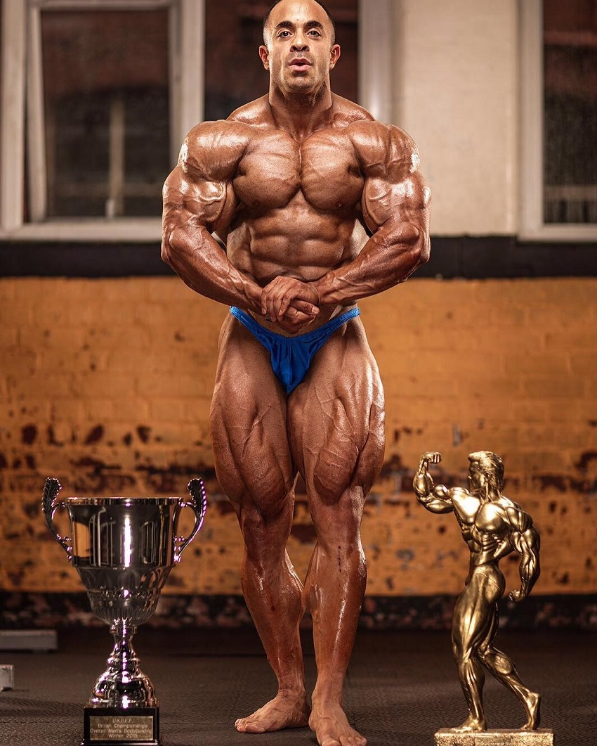 Sasan Heirati posing with his trophies, looking ripped and muscular