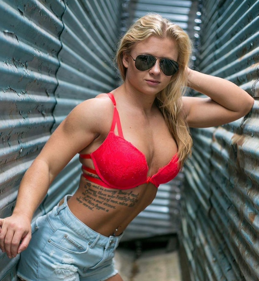 Shelby Dueitt posing with sunglasses on, showing off her lean upper physique