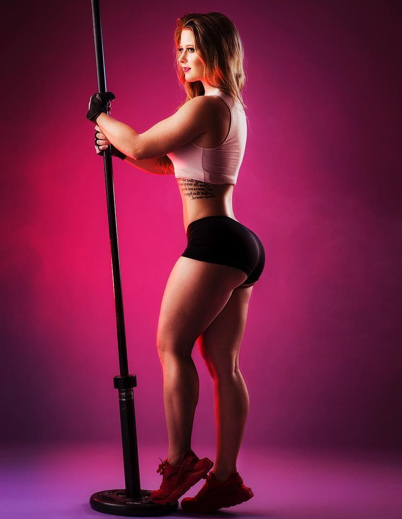 Shelby Dueitt posing with a barbell looking fit and lean