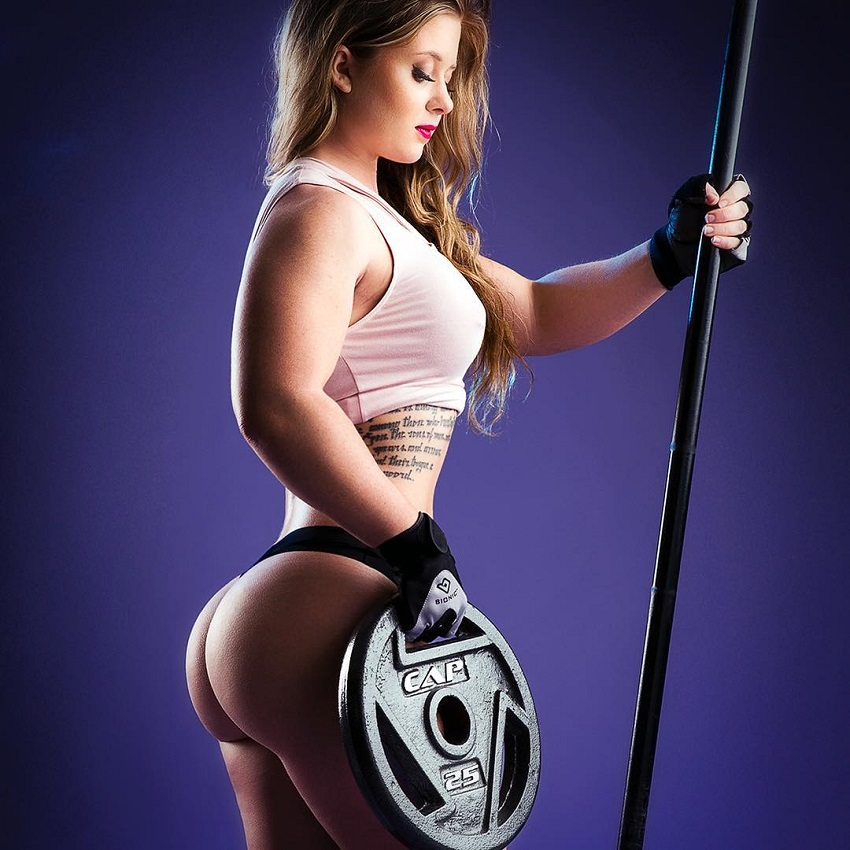 Shelby Dueitt posing in a photo shoot with a barbell and weight plate in her hands, looking curvy, fit, and lean