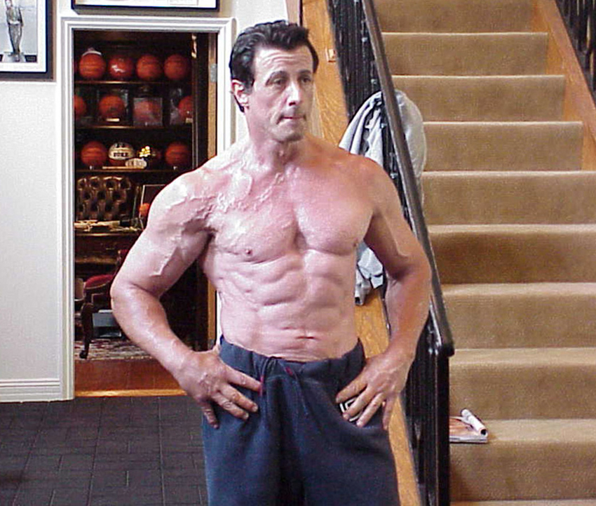 Sylvester Stallone posing at home topless looking ripped and muscular