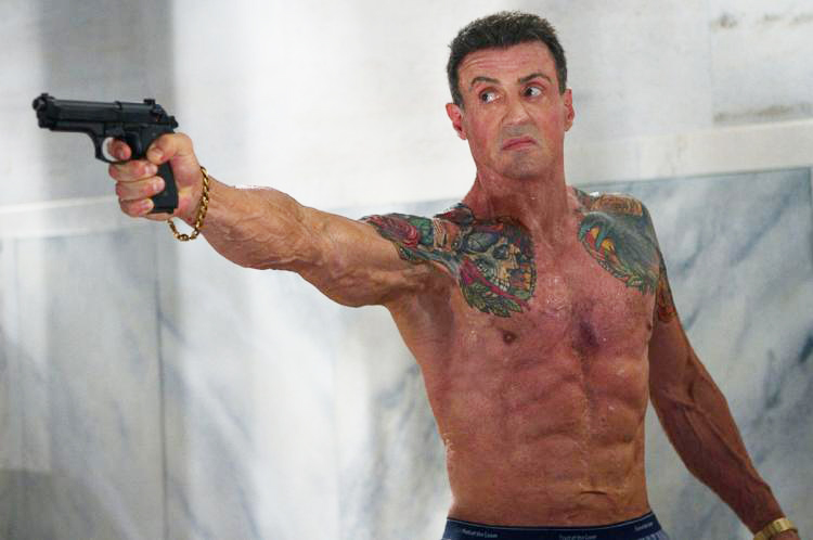 Sylvester Stallone holding a gun shirtless in a film looking lean and muscular