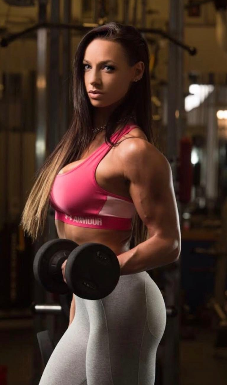 Amy Leigh-Quine doing dumbbell curls as a part of a photo shoot looking lean and fit