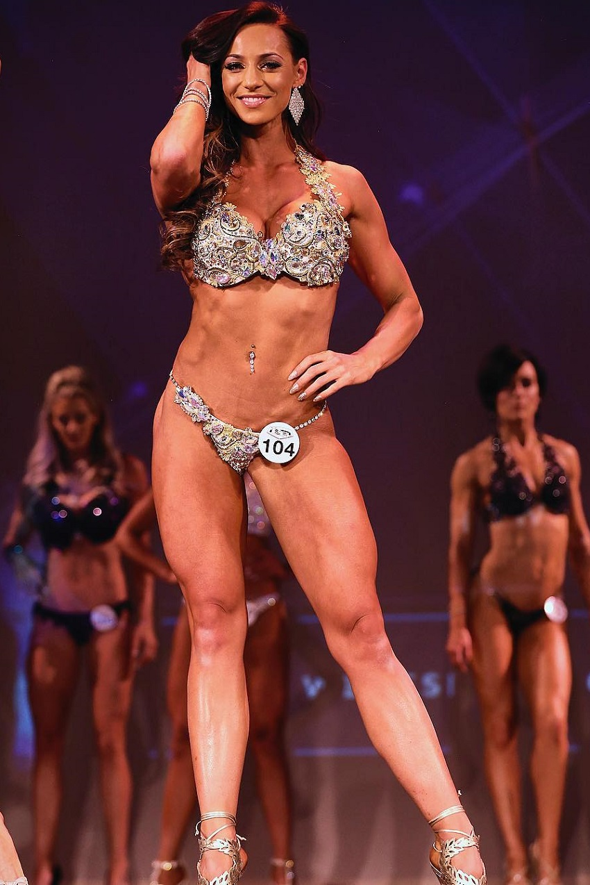 Amy Leigh-Quine competing on the WBFF stage looking fit and lean