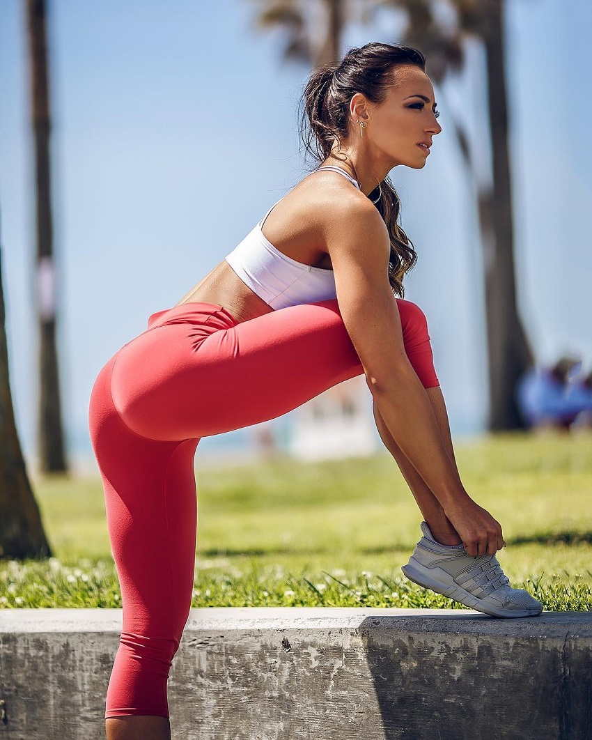 Amy Leigh-Quine tying her shoelaces outdoors wearing red yoga pants looking lean and fit