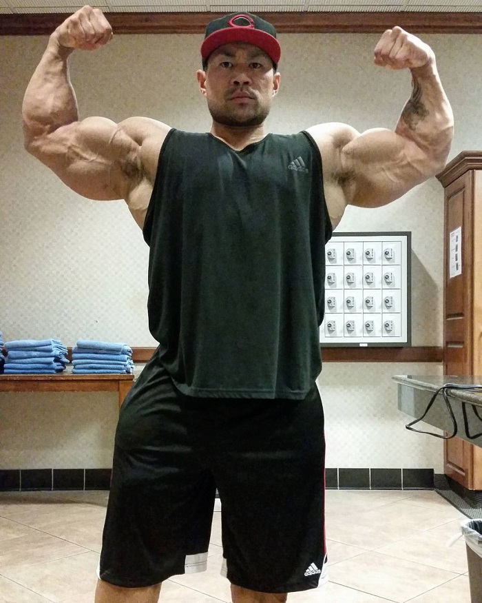 An Nguyen doing a front double biceps flex for a photo