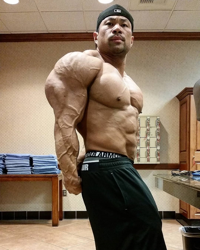 An Nguyen performing a side triceps pose for a camera looking huge