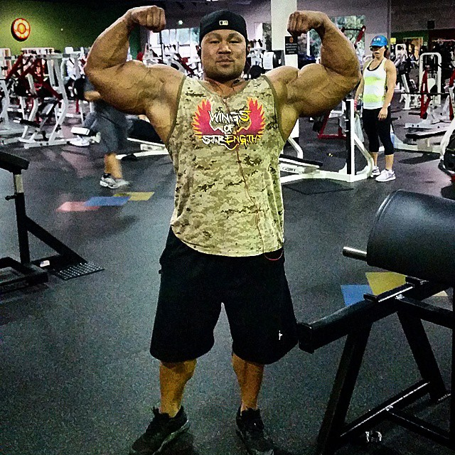 An Nguyen flexing his biceps in a gym for a photo