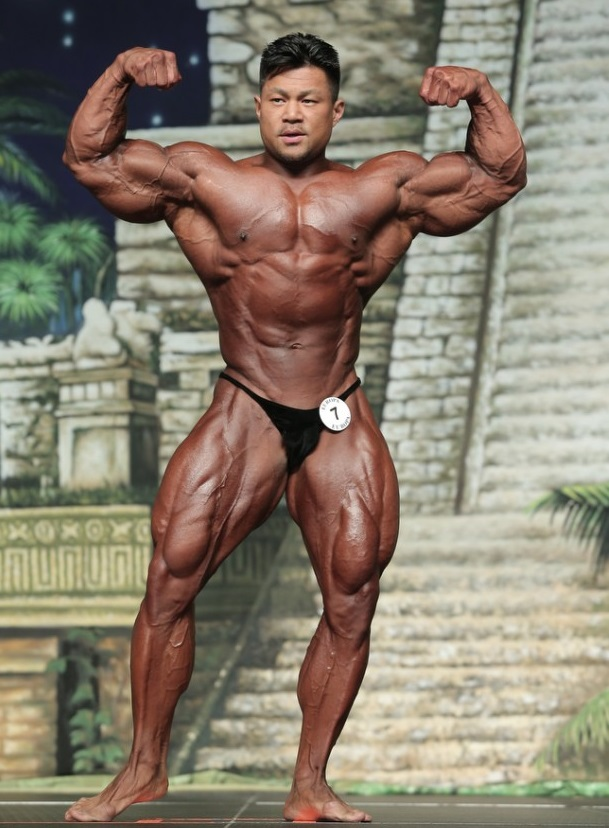 An Nguyen doing a front double biceps pose on a bodybuilding stage