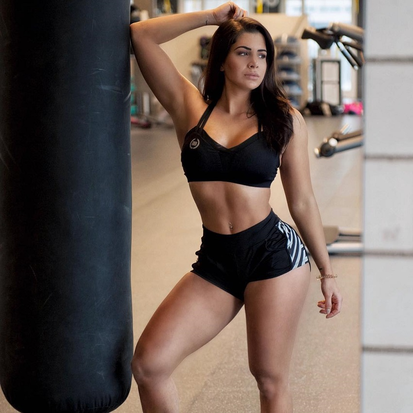 Andrina Santoro posing by the boxing bag wearing sports clothes looking fit