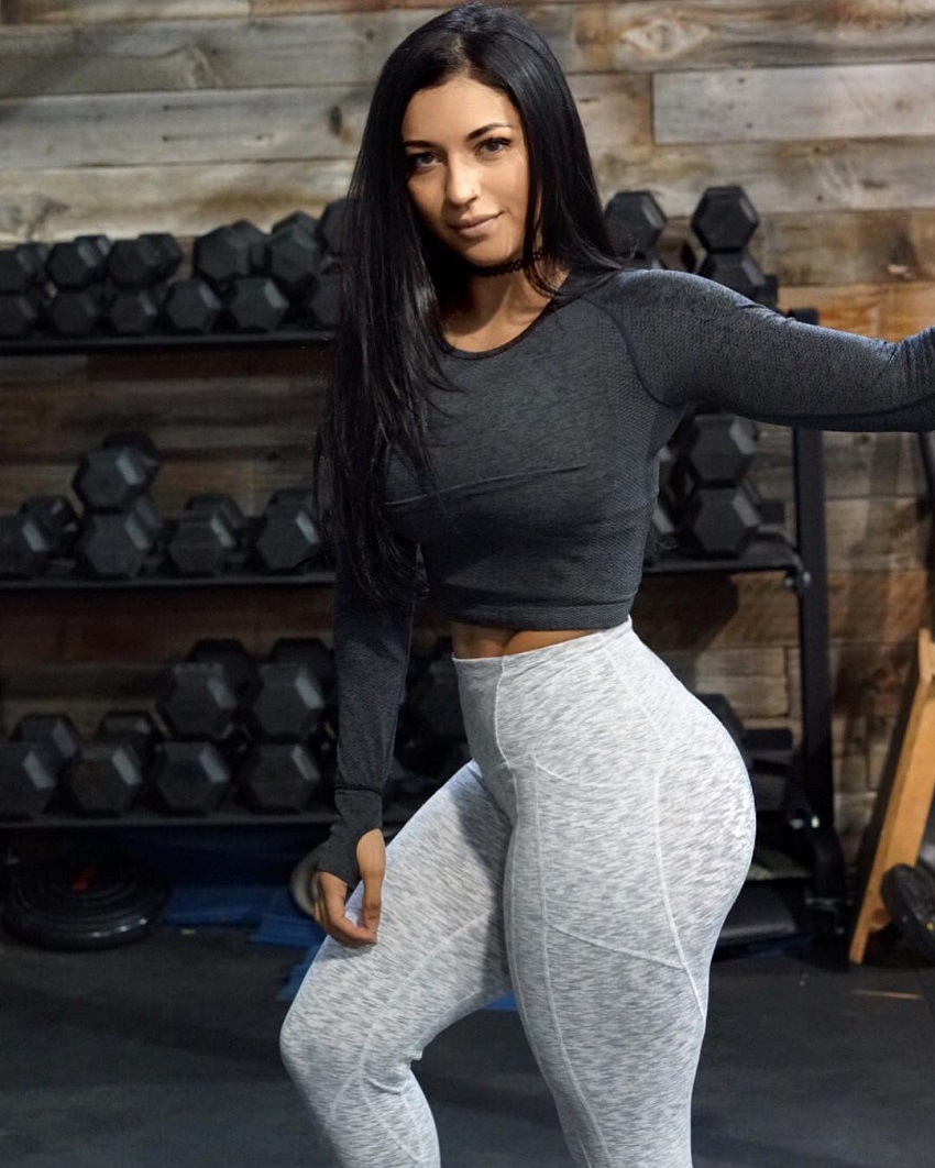 Bianca Taylor standing in a gym in front of a dumbbell rack and posing for a photo