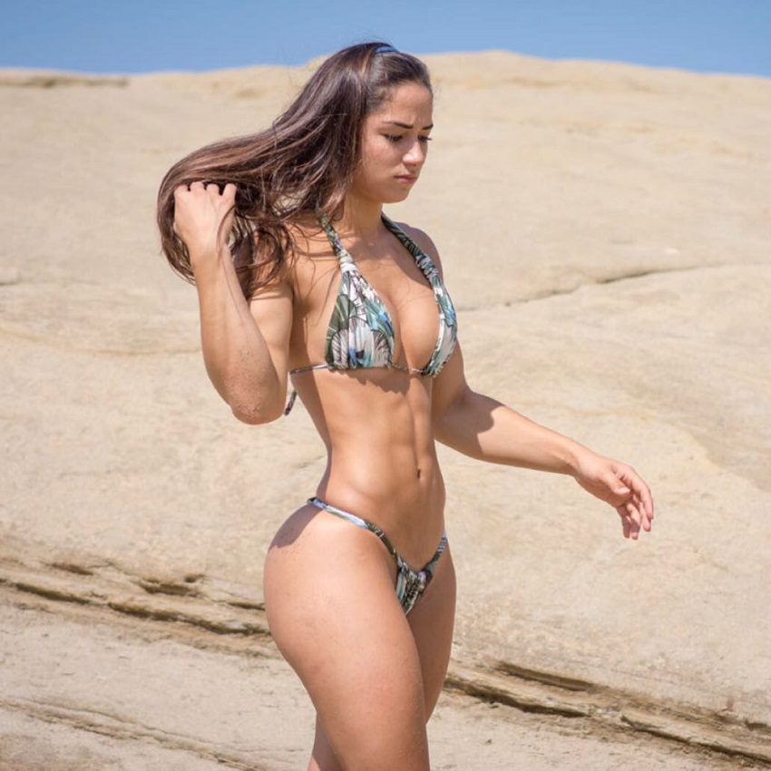 Bruna Luccas walking by a big rock in a bikini looking fit and lean