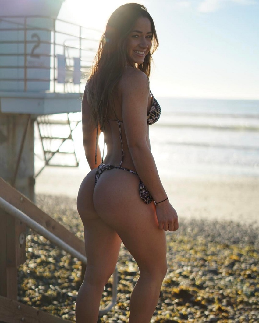 Bruna Luccas standing on the beach posing for a photo looking fit and lean