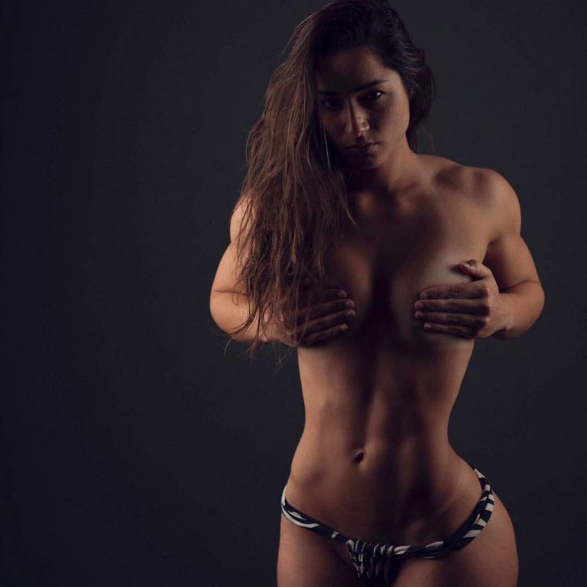 Bruna Luccas covering her naked breasts with her arms looking fit and strong