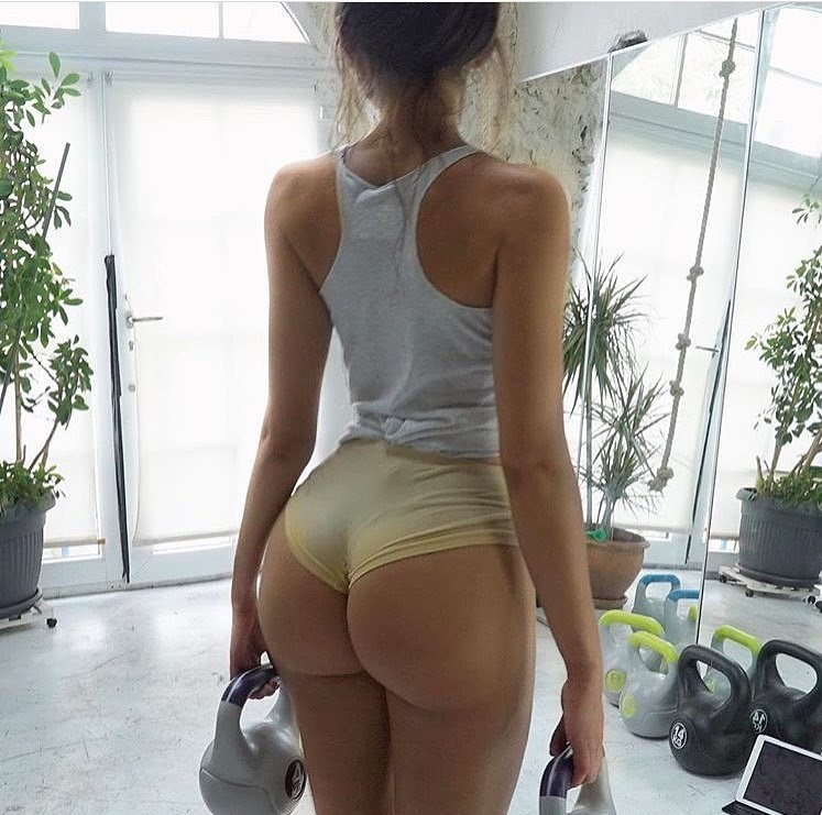 Carinnha White showcasing her curvy glutes while holding kettlebells in her hands