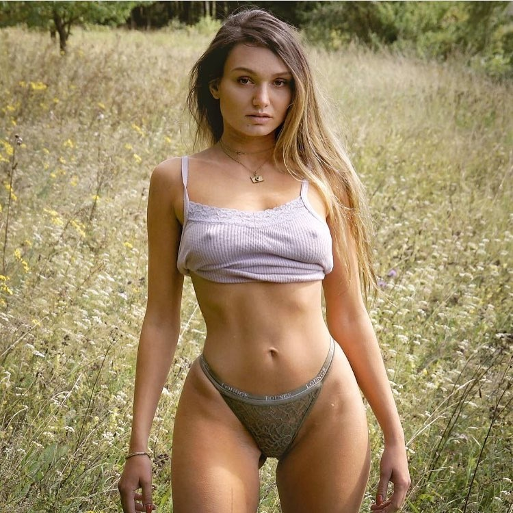 Carinnha White posing in a field of grass looking fit and lean