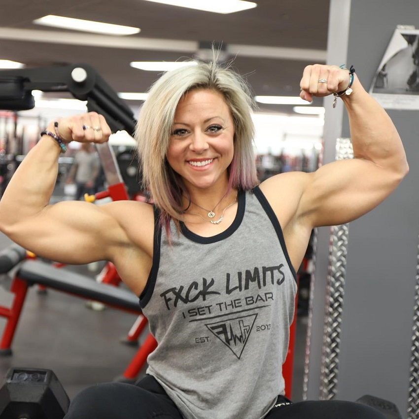 Dani Reardon wearing a tank top, smiling and flexing her biceps for a photo